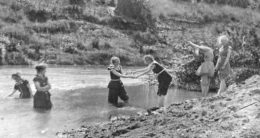 Early Masterton swimmers braving the cold waters of a local rivers, clad in swim suits to their knees.